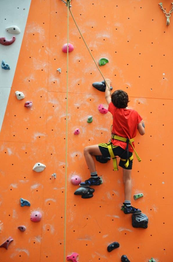 Ijl tiener met uitrusting beklimmend verticale muur stock fotografie
