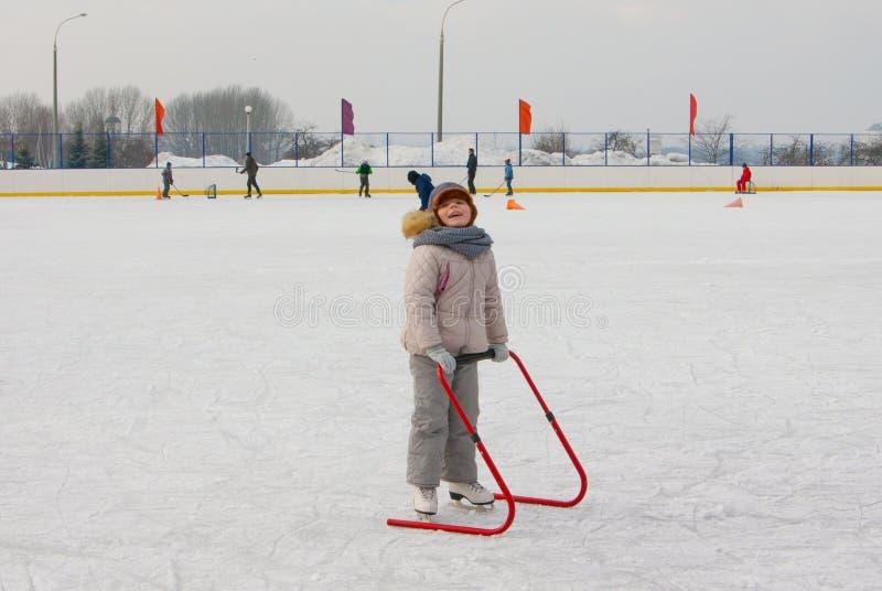 Ijs die met kindersteun apparaat schaatsen stock afbeelding