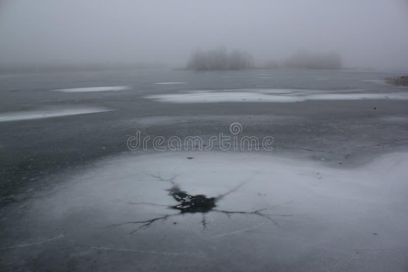 Ijs-gat in Misty Frozen Lake Winter stock afbeelding
