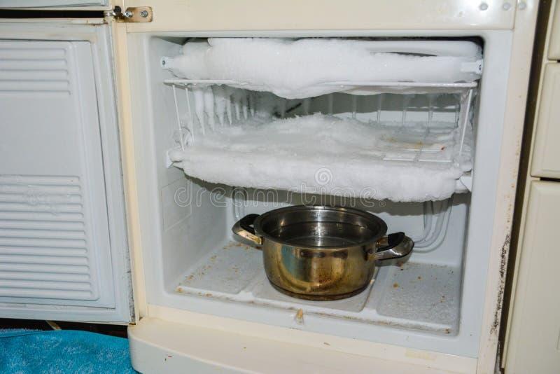 Ijs in koelkast, behoefte het ontdooien, bevroren ijskast, stock foto