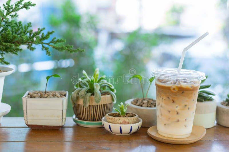 Ijs latte koffie met groene aard op houten lijst stock foto