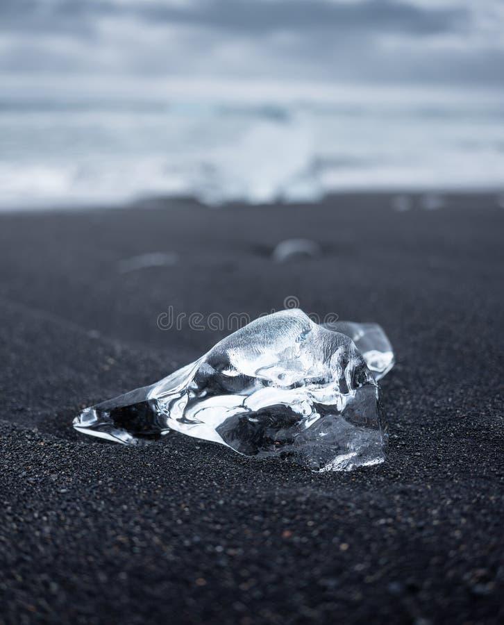 Ijs op het zwarte zand op het strand, IJsland Oceaanbaai en ijsbergen Landschappen in IJsland royalty-vrije stock afbeeldingen
