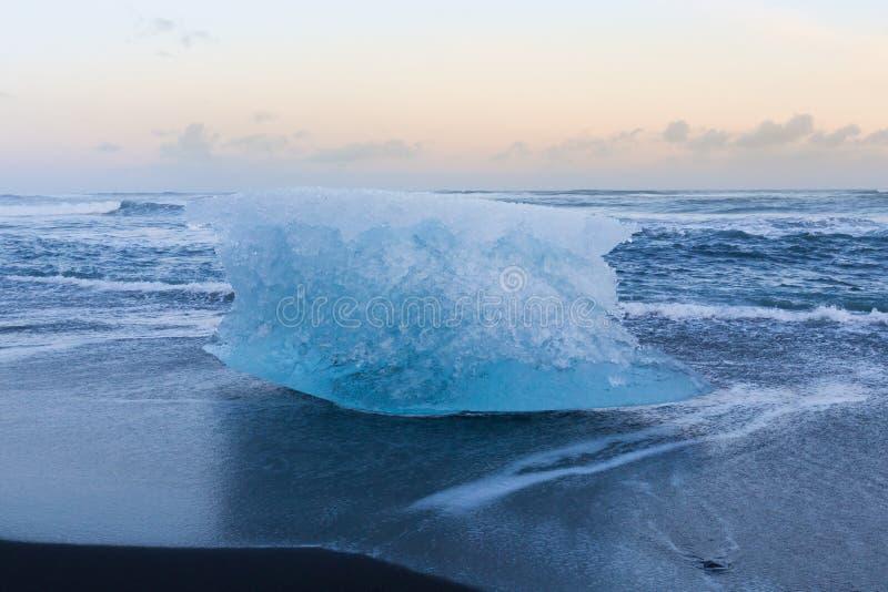 Ijs op zwarte zandstrand en horizon die wordt gekubeerd stock fotografie