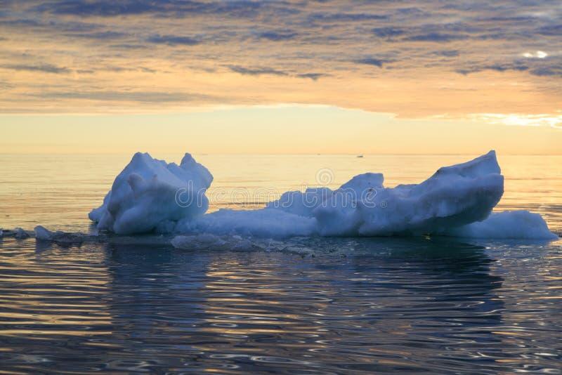 Ijs in zeewater tegen de zonsonderganghemel stock foto