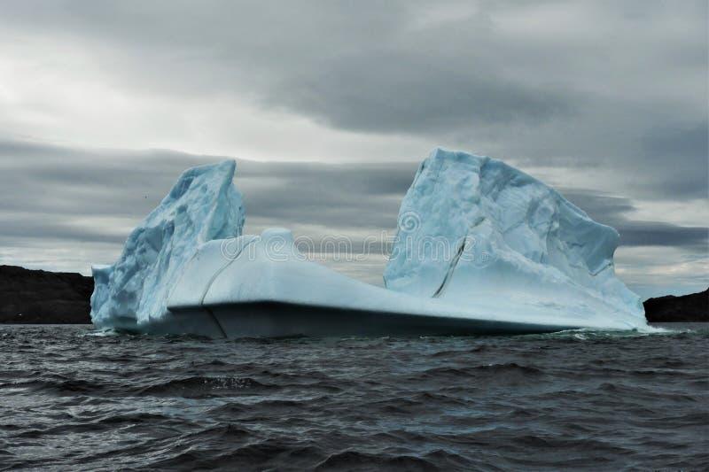 Ijsberg die in Water op Bewolkte Dag drijven royalty-vrije stock fotografie
