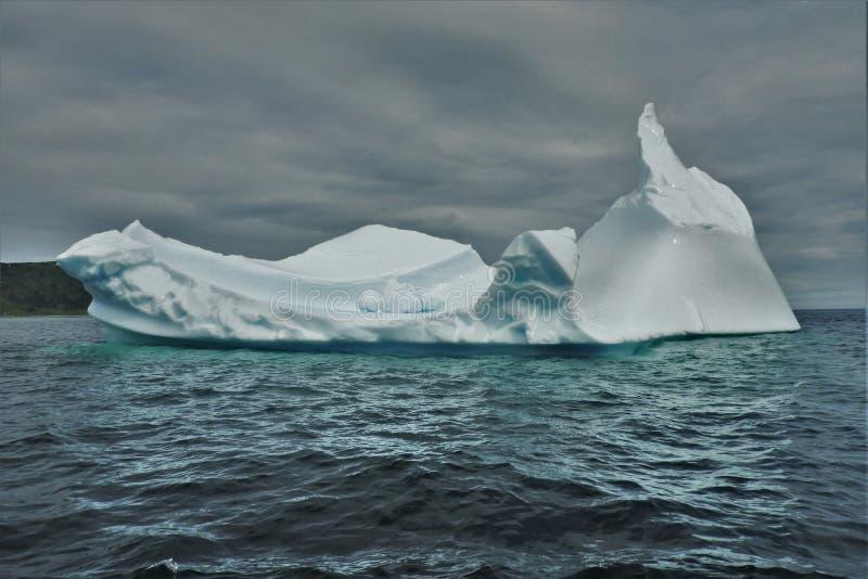 Ijsberg die in Water op Bewolkte Dag drijven royalty-vrije stock afbeelding