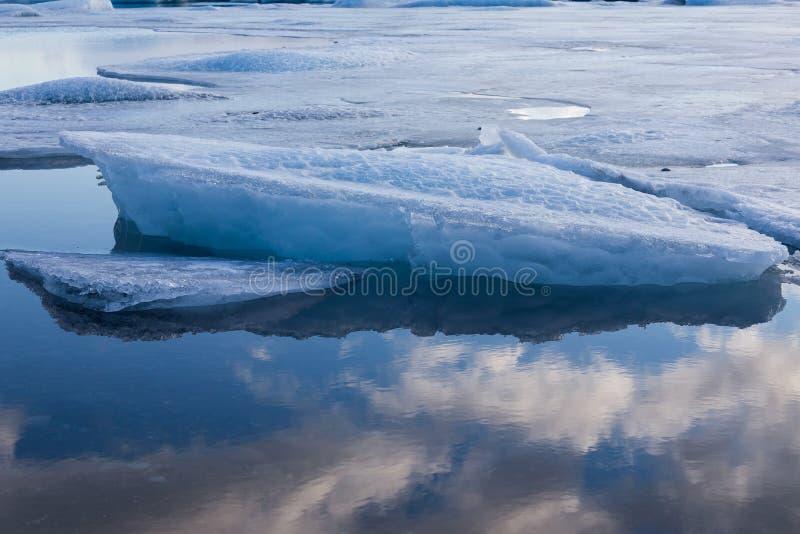 Ijsberg het breken over ijsvloer met blauwe hemelbezinning stock afbeeldingen