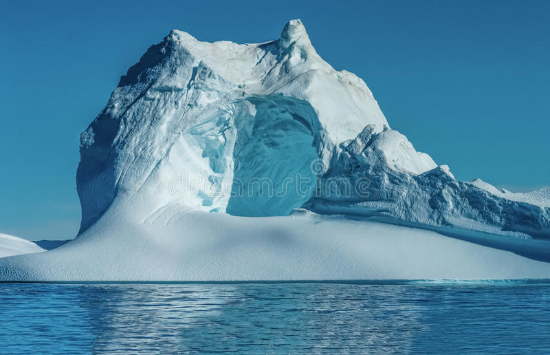 Ijsberg met een reusachtig hol bij de mond van Icefjord in Ilulissat, Groenland stock foto's