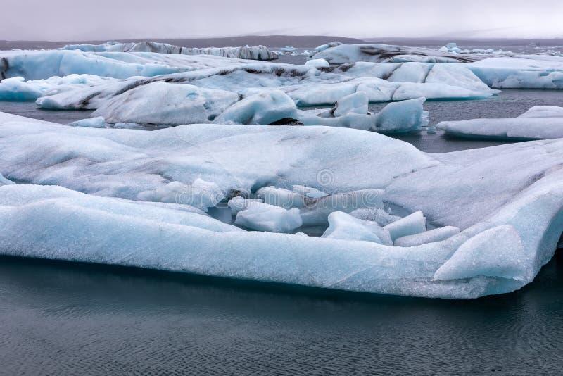 Ijsbergen die in Jokulsarlon-Lagune door de zuidelijke kust o drijven stock foto