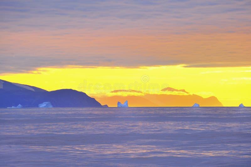 Ijsbergen en gouden hemel royalty-vrije stock foto's