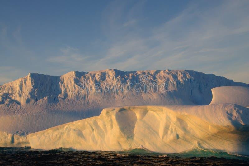 Ijsbergen in het avond licht stock fotografie