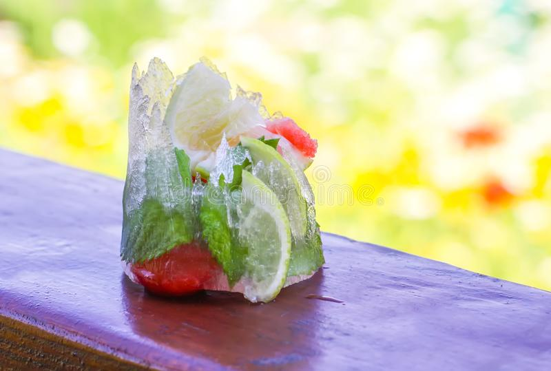 Ijsblokje met aardbei, citroen en verse muntbladeren op houten oppervlakte in openlucht stock foto