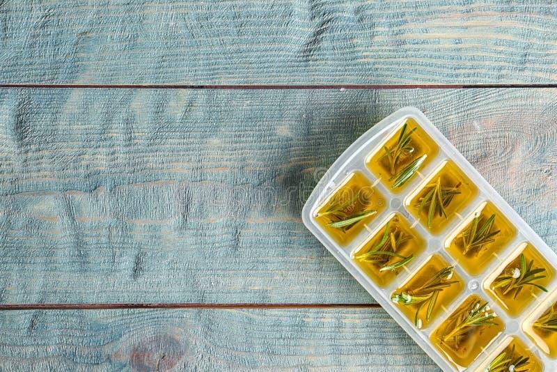 Ijsblokjedienblad met rozemarijn en olijfolie op houten achtergrond, hoogste mening royalty-vrije stock foto's