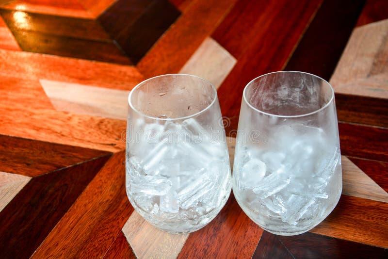 ijsblokjes in een lege bril met water op een houten tafel achtergrond royalty-vrije stock foto's