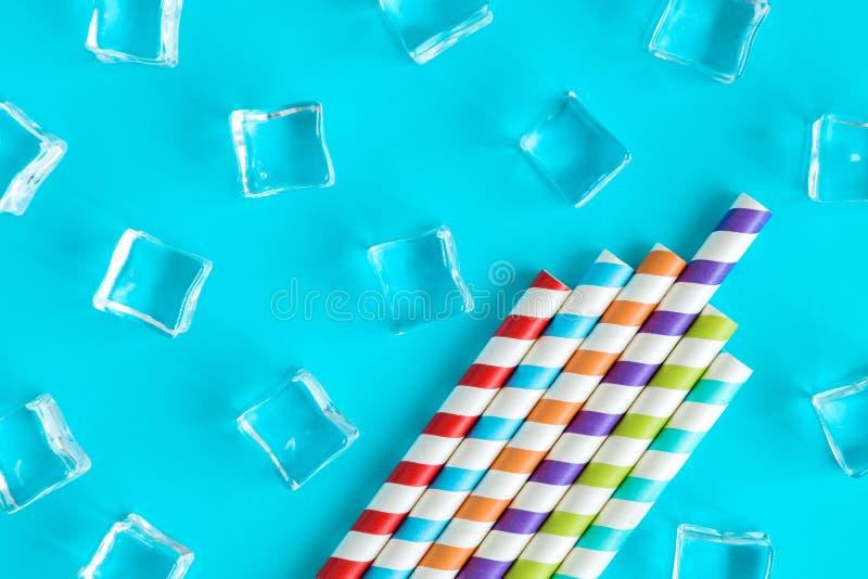 Ijsblokjes en gestripte die multicolored het drinken strosamenvatting op blauw worden geïsoleerd stock foto's