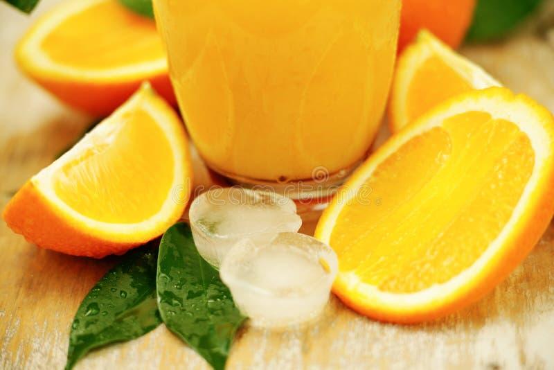 Ijsblokjes en jus d'orange stock afbeelding