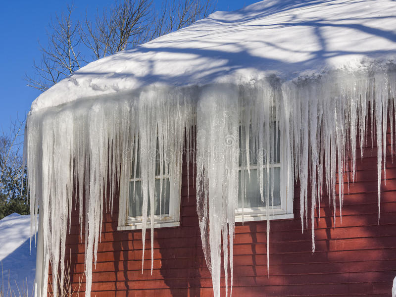 Ijsdammen en sneeuw op dak en goten royalty-vrije stock afbeeldingen