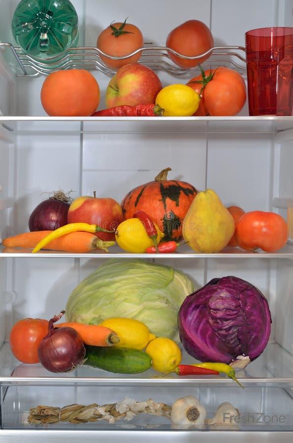 Ijskastplanken met vruchten, groenten en water royalty-vrije stock foto