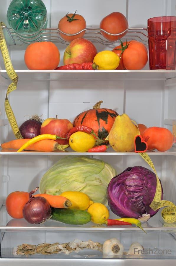 Ijskastplanken met vruchten, groenten, water en maatregel stock foto