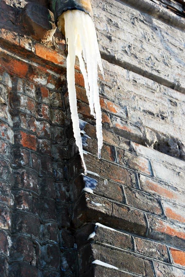 Ijskegel van rioolbuis, muur met rode bakstenen onder ijs, grunge achtergrond stock fotografie