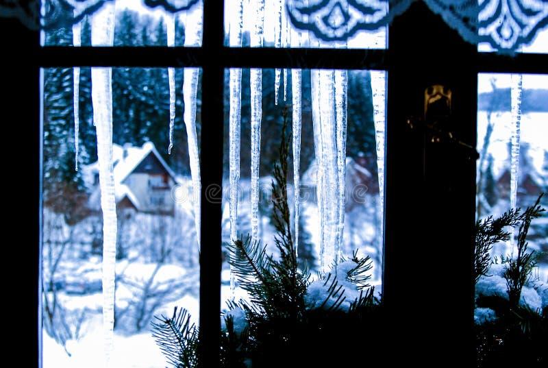Ijskegels achter het venster stock afbeeldingen