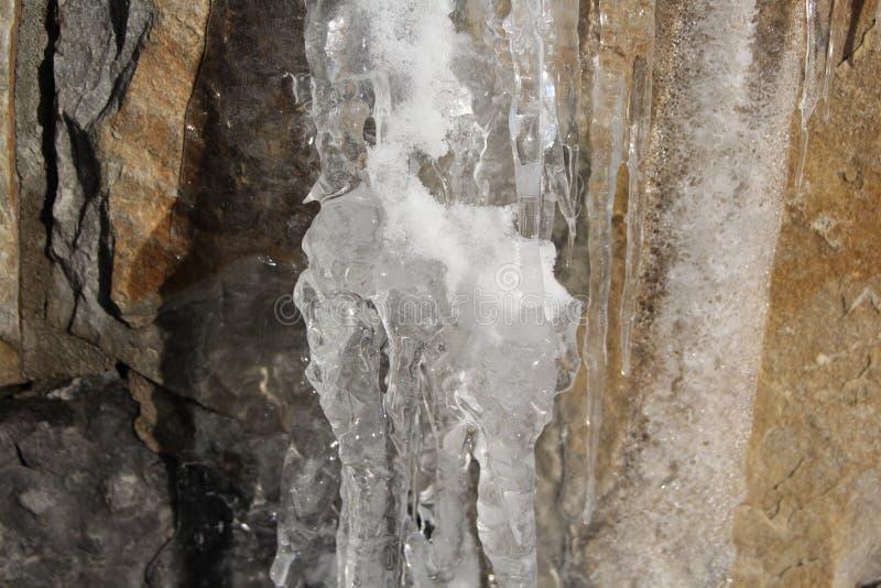Ijskegels die op een richel met rotsachtige bacground hangen stock afbeelding