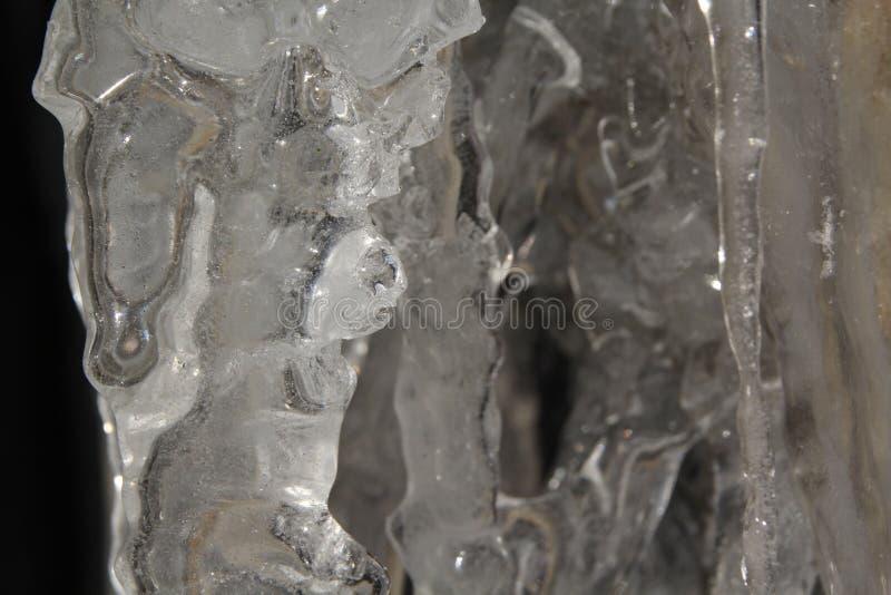 Ijskegels die op een richel met rotsachtige bacground hangen royalty-vrije stock afbeelding