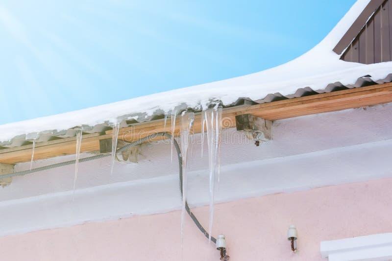 Ijskegels die op het dak onder de heldere zonnestralen van de lente hangen royalty-vrije stock afbeeldingen