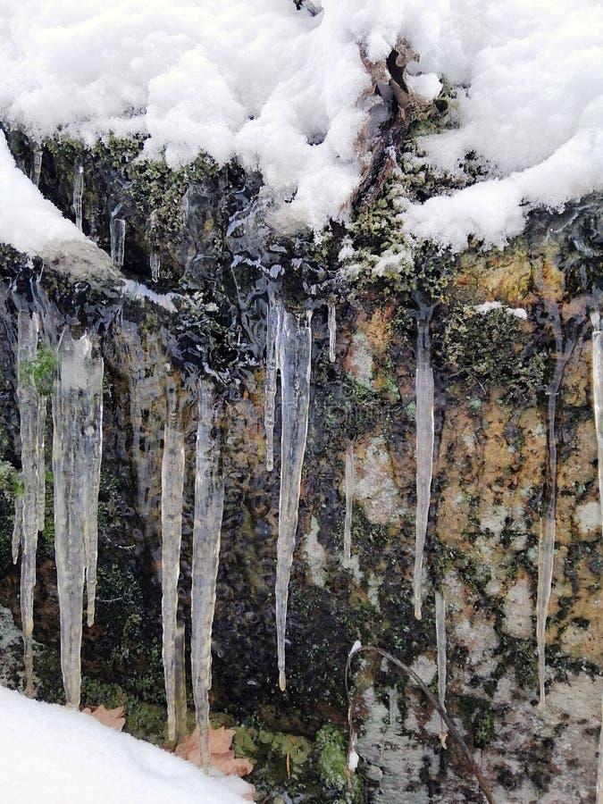Ijskegels en sneeuw op de stenen royalty-vrije stock fotografie