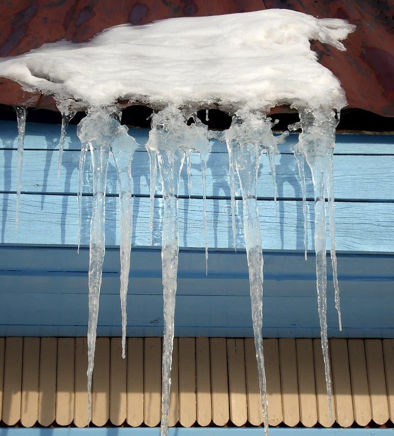 Ijskegels op het dak van het huis stock fotografie