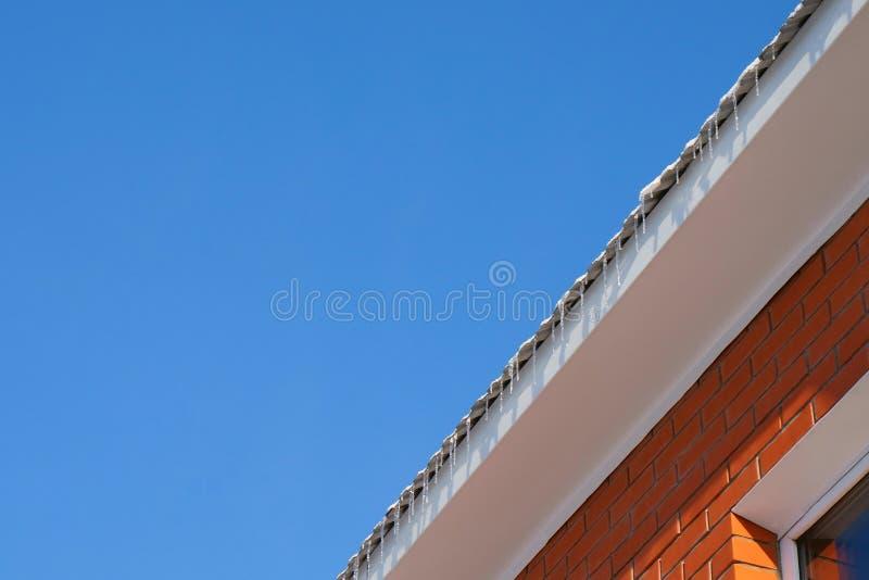 Ijskegels op het dak van het huis, blauwe hemel stock foto