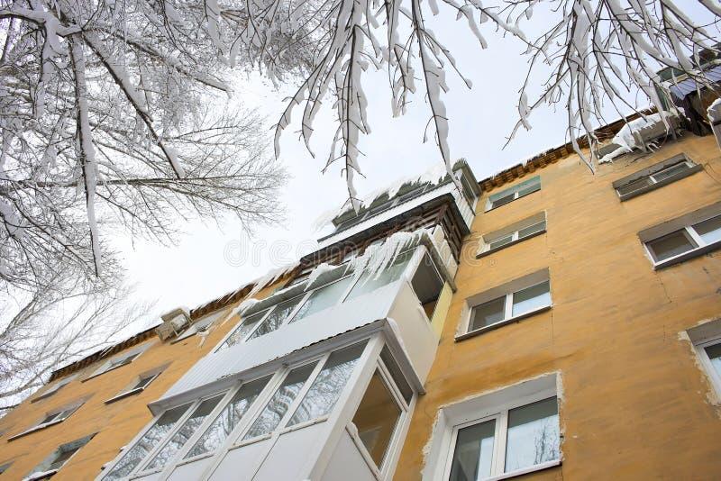 Ijskegels van het dak, verglaasd balkon van een woningbouw in Saratov stock afbeelding