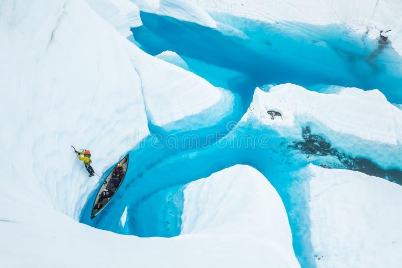 Ijsklimmer die een klim opstarten uit een kano op een blauwe pool op een gletsjer in Alaska royalty-vrije stock foto