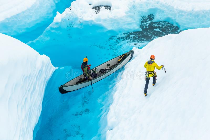 Ijsklimmer die langs steile helling van gletsjerijs lopen boven een kano in een blauwe pool stock afbeelding
