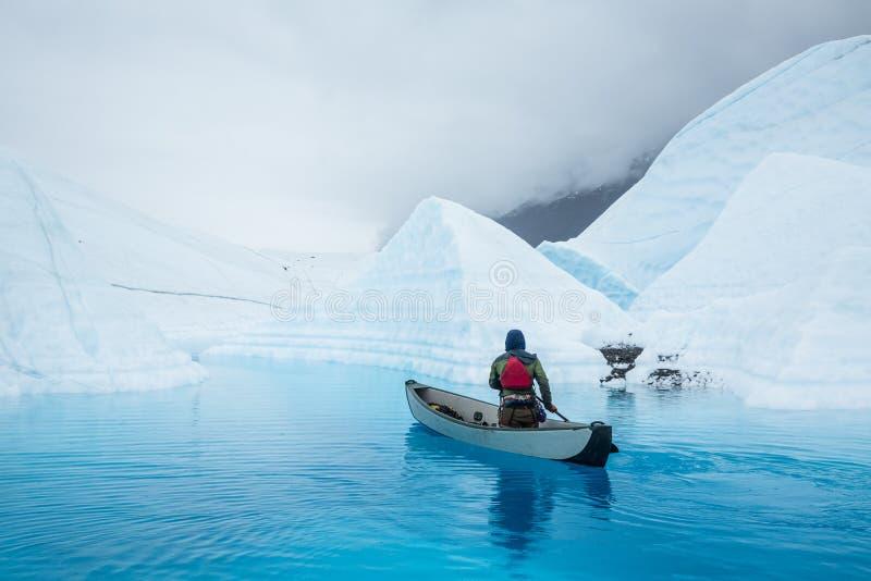 Ijsklimmer die in opblaasbare kano over een gletsjermeer paddelen bovenop de Matanuska-Gletsjer in Alaska stock foto's