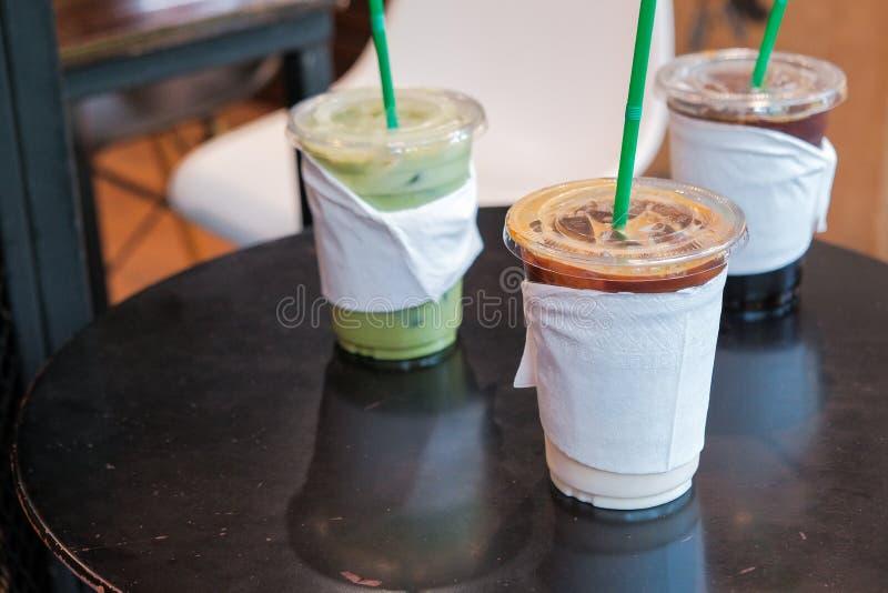 Ijskoffie en koude drank van de matcha de groene thee in meeneem of om te gaan kop op houten lijst stock afbeeldingen