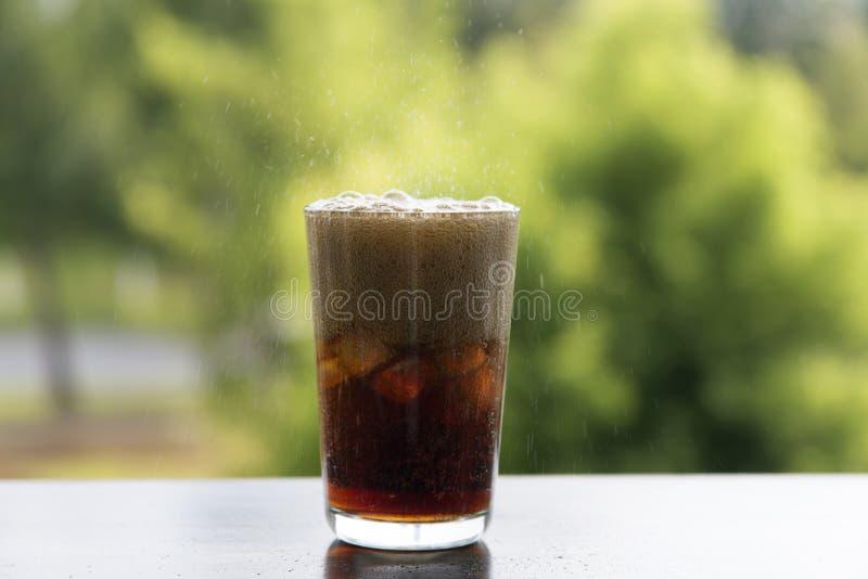 Ijskola met het bespatten van Co-bellen De drank met ijs, close-up, die bruist bruist stock fotografie
