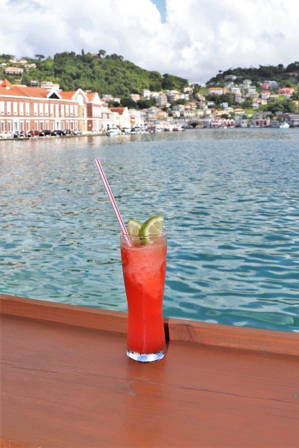 Ijskoude drank op een spoor met oceaan en tropische eilandscènes op de achtergrond stock foto