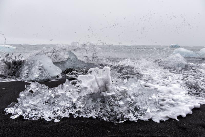 Ijskristal op beroemd zwart zandstrand en oceaangolven, een deel van ijsbergen van Jokulsarlon-gletsjerlagune, Diamantstrand, IJs stock fotografie