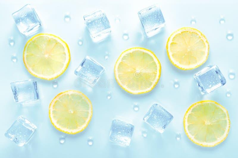 IJskubben en vers citroensegment met waterdruppels op blauwe achtergrond stock fotografie