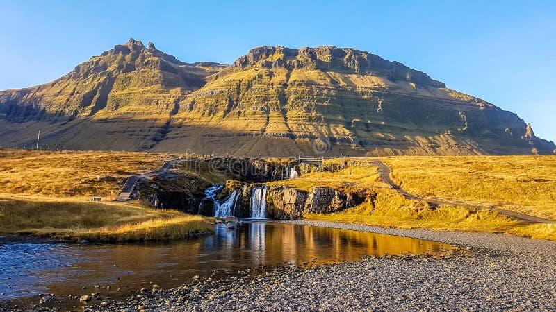 IJsland - een overweldigende waterval met lange erachter bergen royalty-vrije stock afbeeldingen