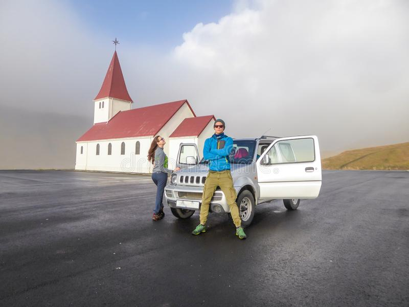IJsland - een paar die die voor een auto blijven door een kleine kerk wordt geparkeerd stock afbeelding