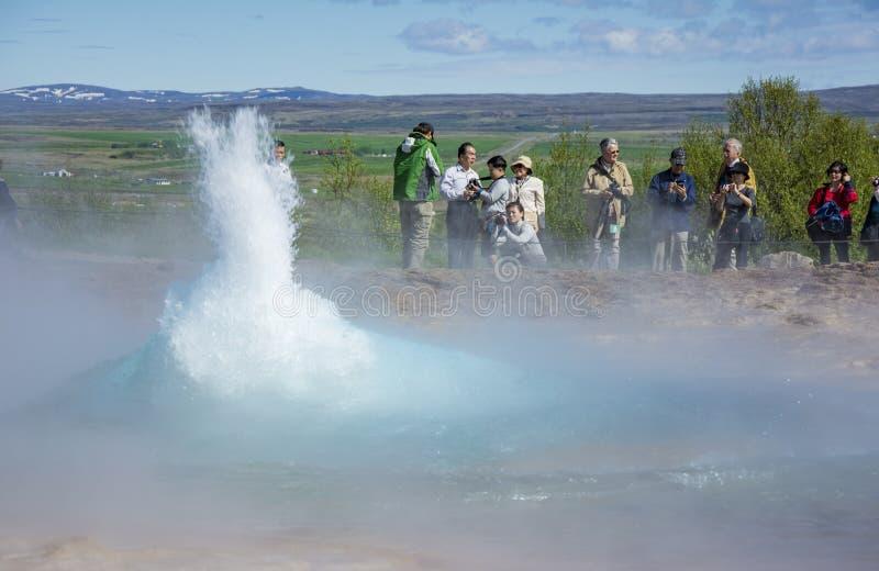 IJsland, Juni 2013: Chinese toerist die Strokkur-geiser bezoeken stock foto