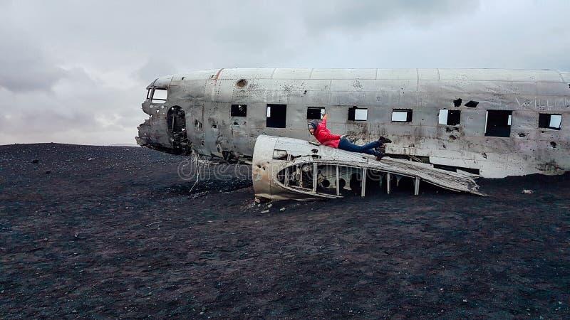 IJsland - Meisje die op een verpletterd vliegtuig op een zwart zandstrand liggen stock foto
