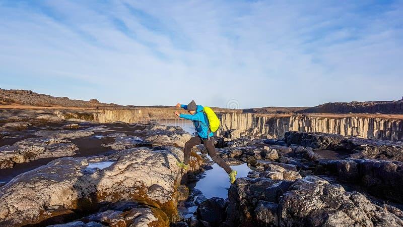 IJsland - Mens die tussen rotsen springen stock afbeelding