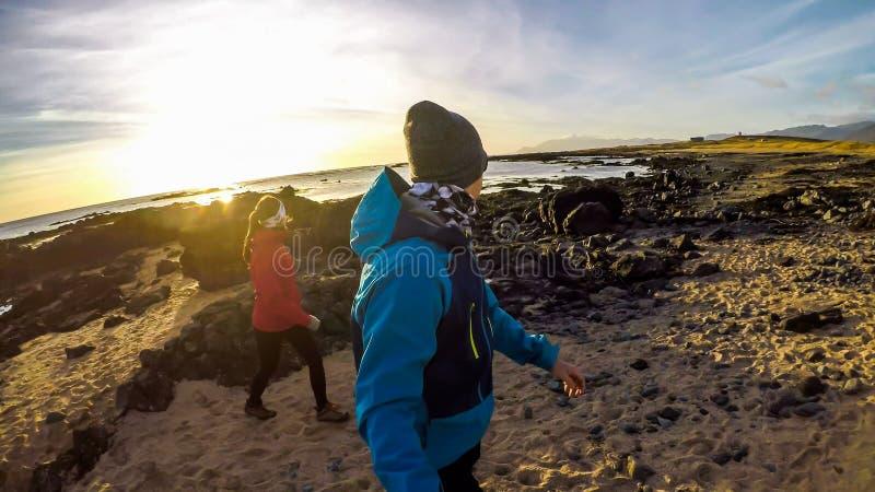 IJsland - Paar die op de kust van een overzees lopen royalty-vrije stock fotografie