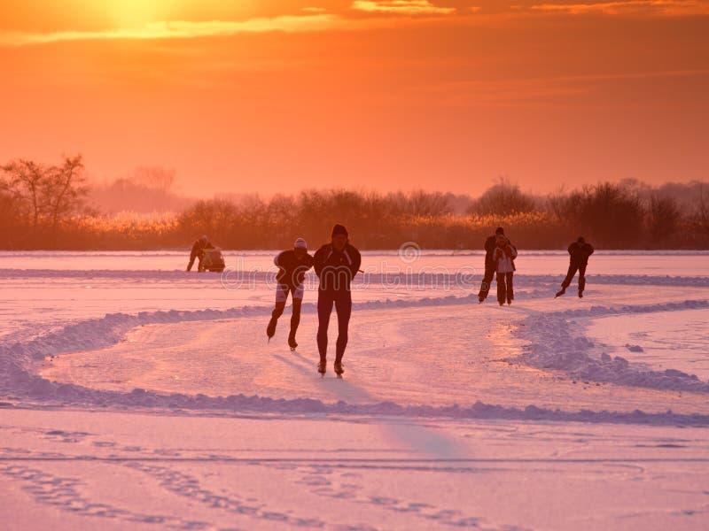 Ijsschaatsers op een bevroren meer stock afbeeldingen