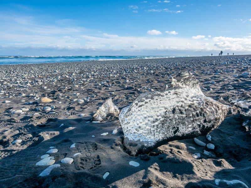 Ijsstukken op zwart zandstrand in IJsland stock foto's