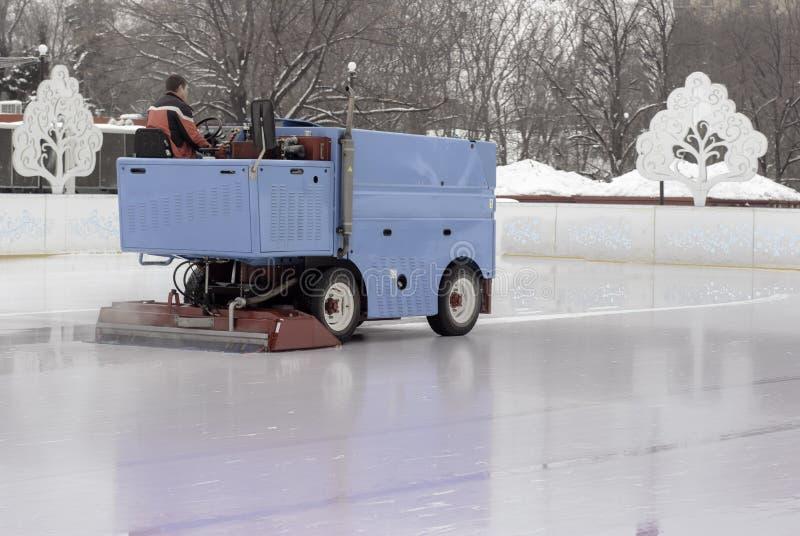 Ijsvoorbereiding bij de piste tussen zittingen in de avond in openlucht/Opgepoetst ijs klaar voor gelijke stock fotografie