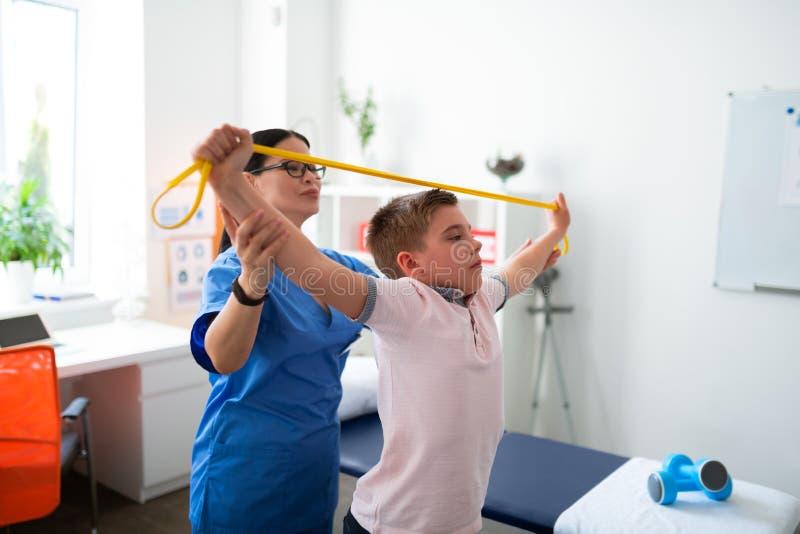 Ijverig kortharig kind die zich in kabinet fysieke therapie bevinden stock foto